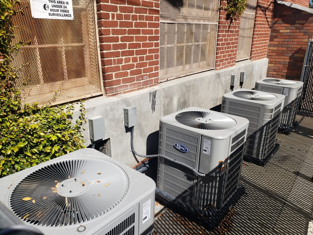 outdoor ACs lined up against brick wall